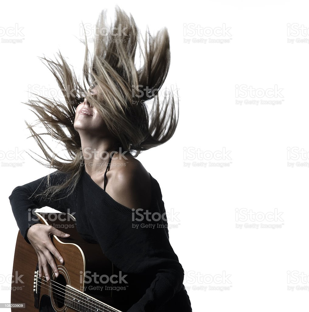Woman Flipping Hair and Holding Guitar stock photo