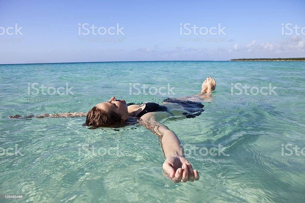 Woman floating and relaxing in the sea royalty-free stock photo