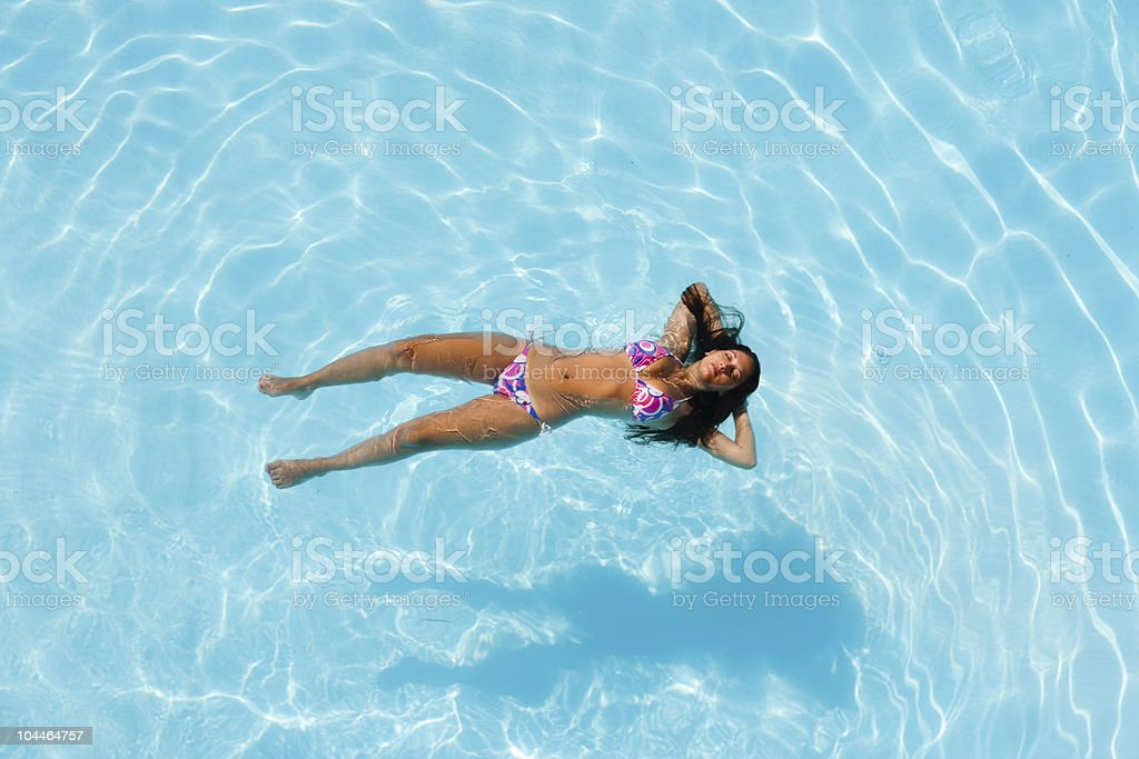 Woman floating in a pool royalty-free stock photo