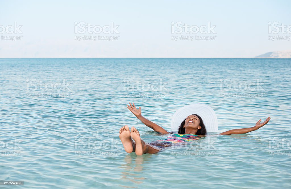 Woman floating in Dead Sea stock photo