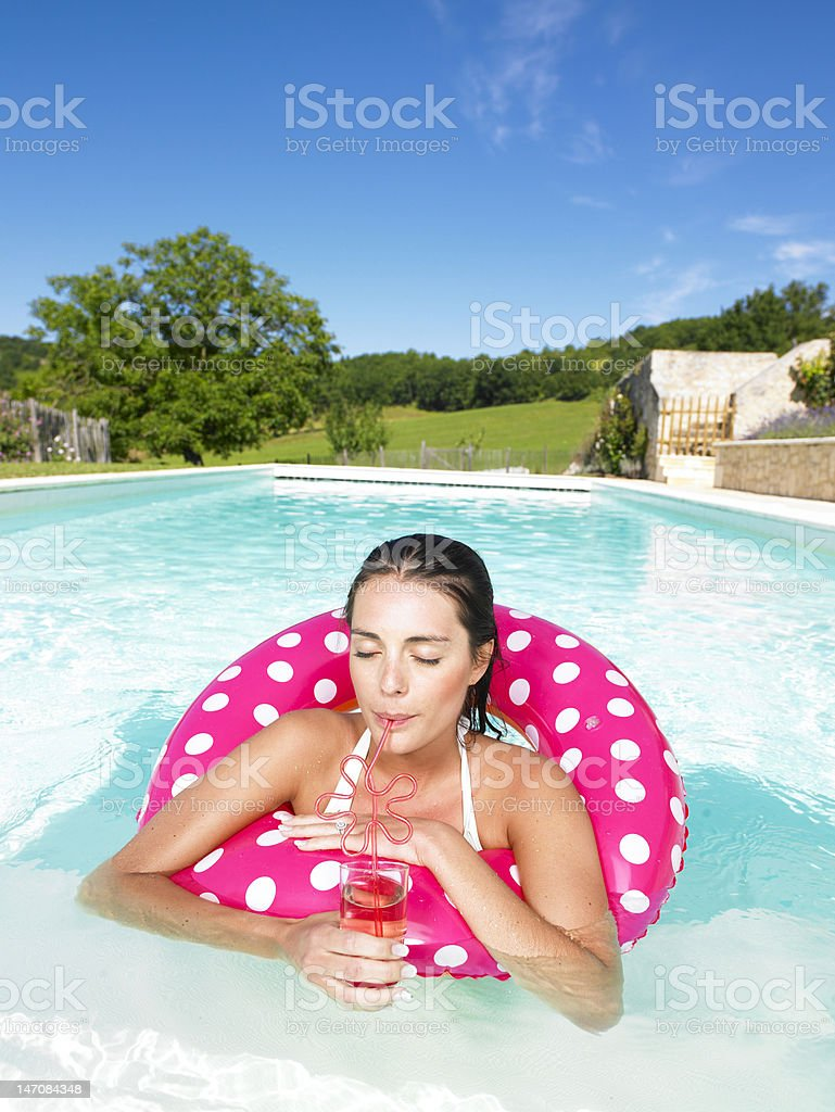 Woman Floating in Pool and Enjoying Drink royalty-free stock photo