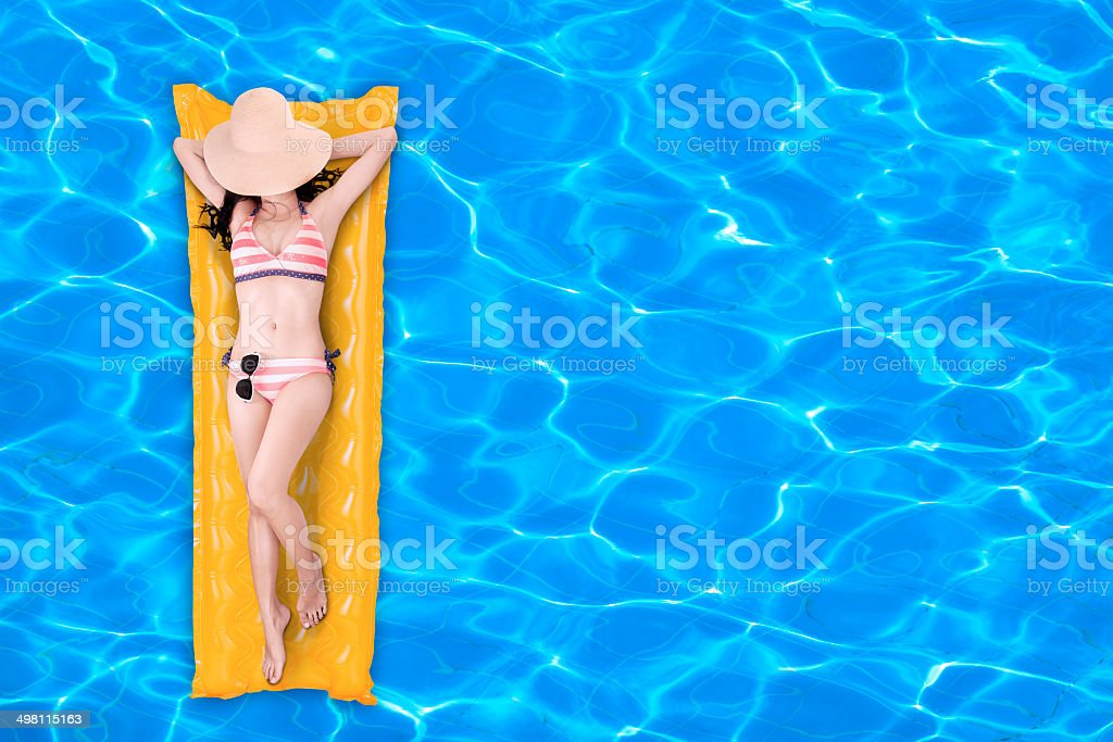 Woman floating on a pool mattress 1 stock photo