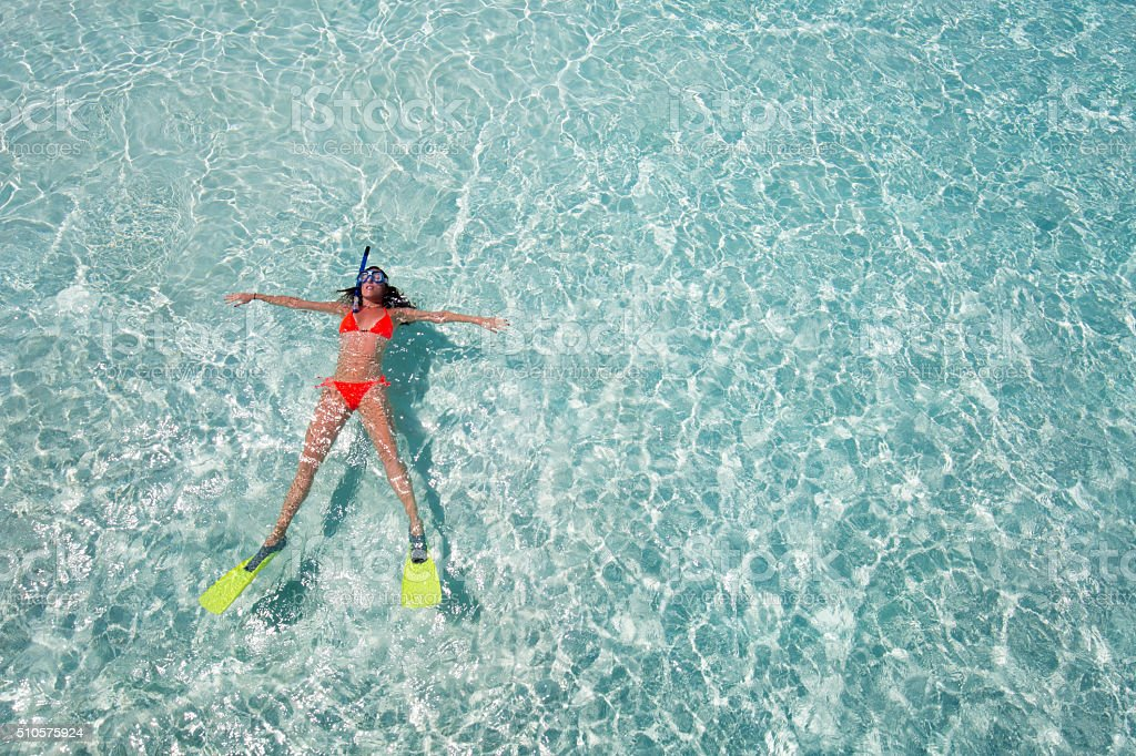 Woman floating on crystal clear waters stock photo