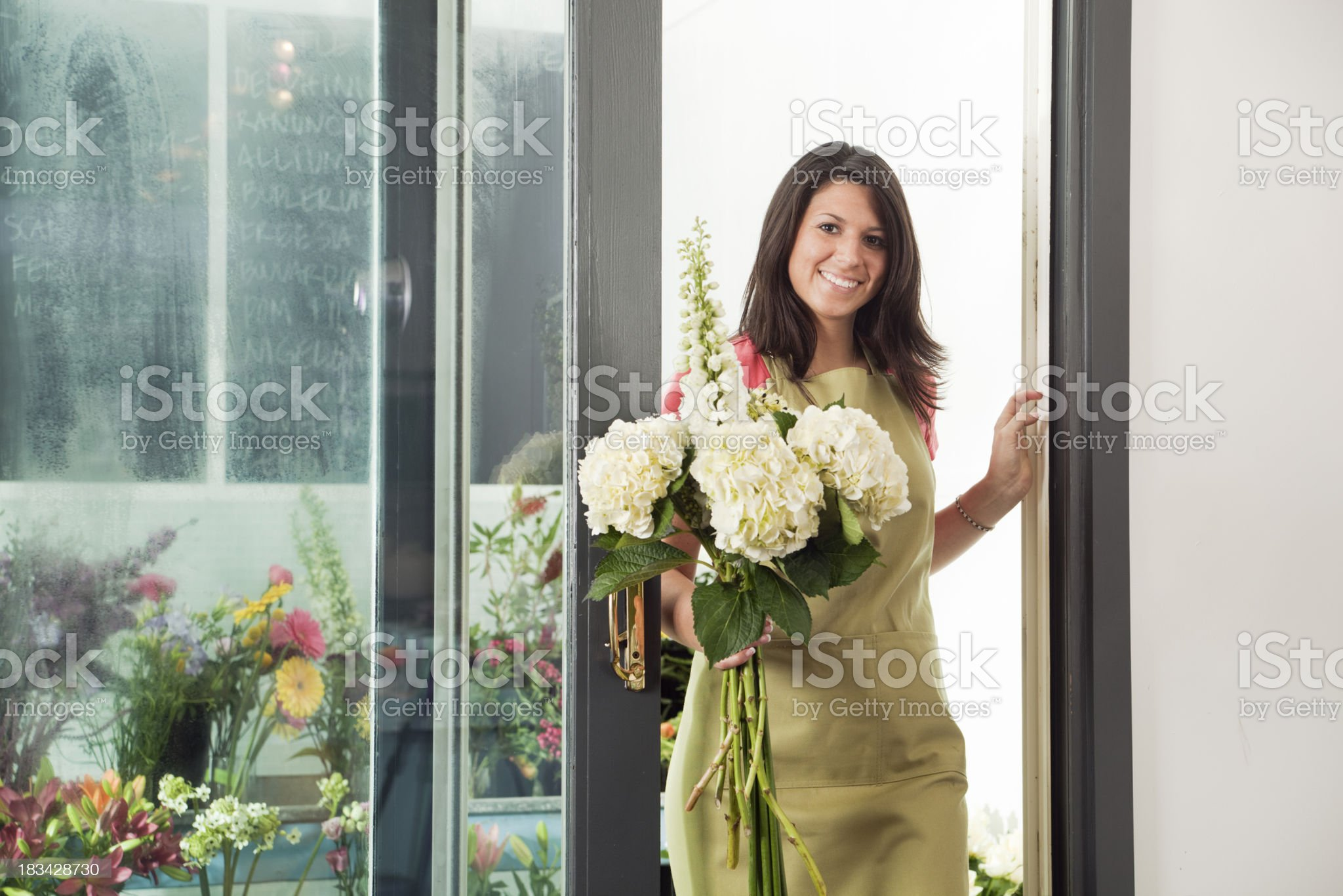Woman Florist at Work, Exiting Refrigerated Cooler with Flower Bouquet royalty-free stock photo