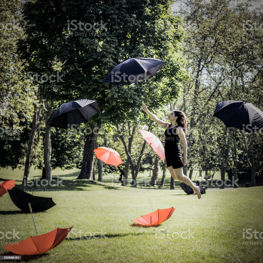 Woman Flying Through The Air Holding An Umbrella stock photo