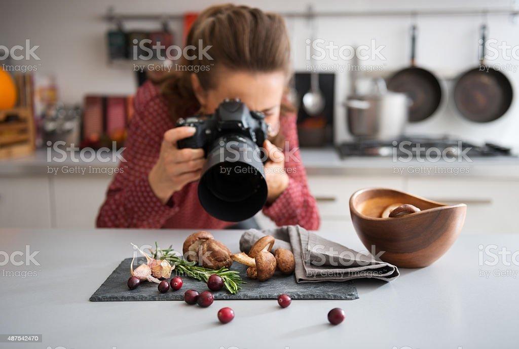 Woman food photographer taking closeup of mushrooms stock photo
