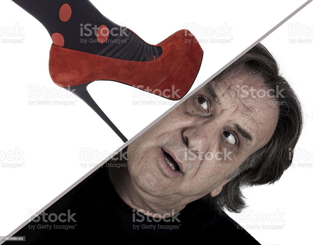 Woman foot crushing man head stock photo