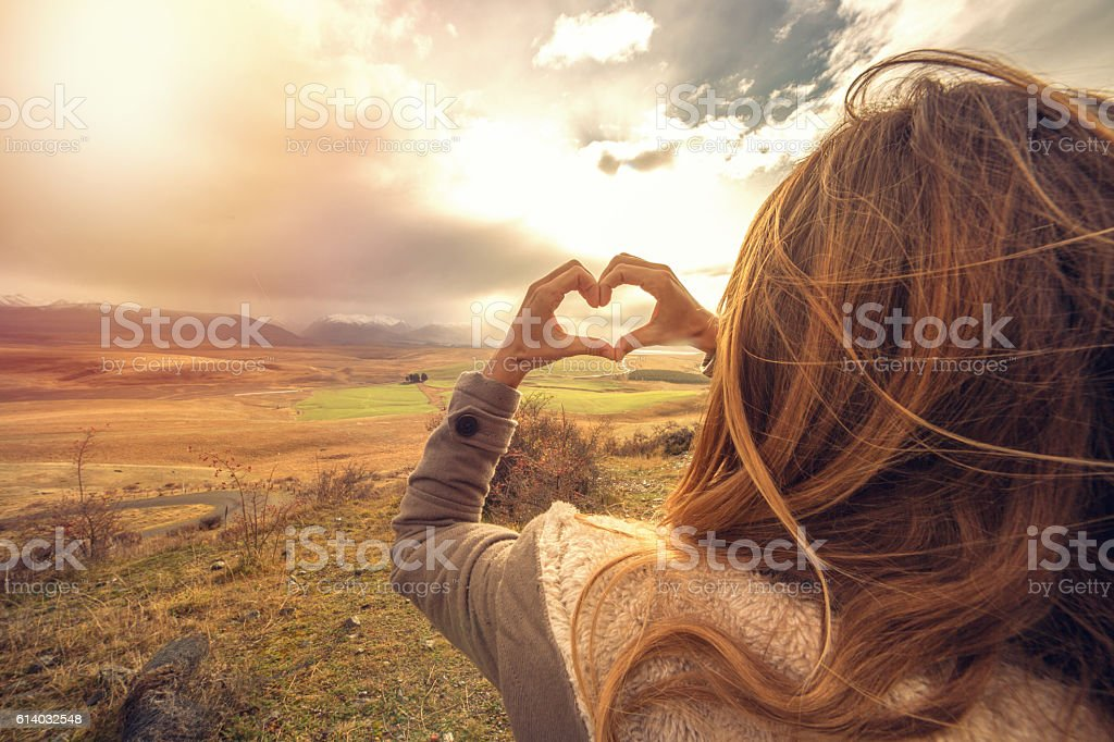 Woman frames nature into heart shape finger frame stock photo