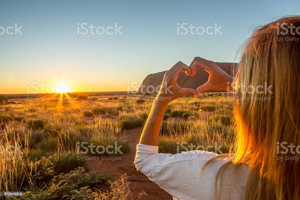 Woman frames sunset into heart shape finger frame stock photo