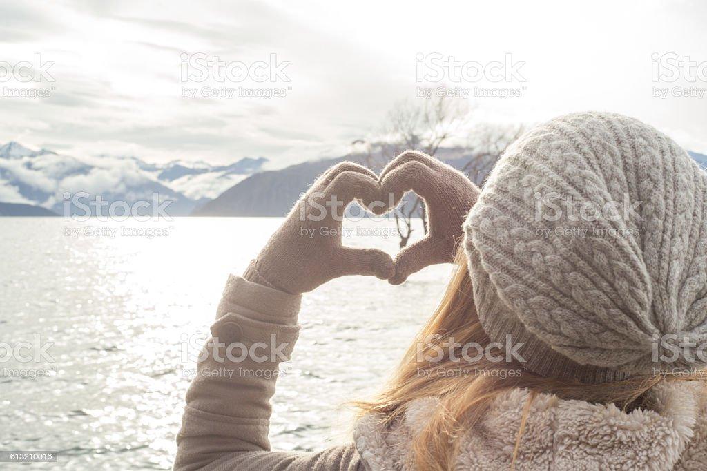 Woman frames the Lone tree at lake Wanaka into heart stock photo
