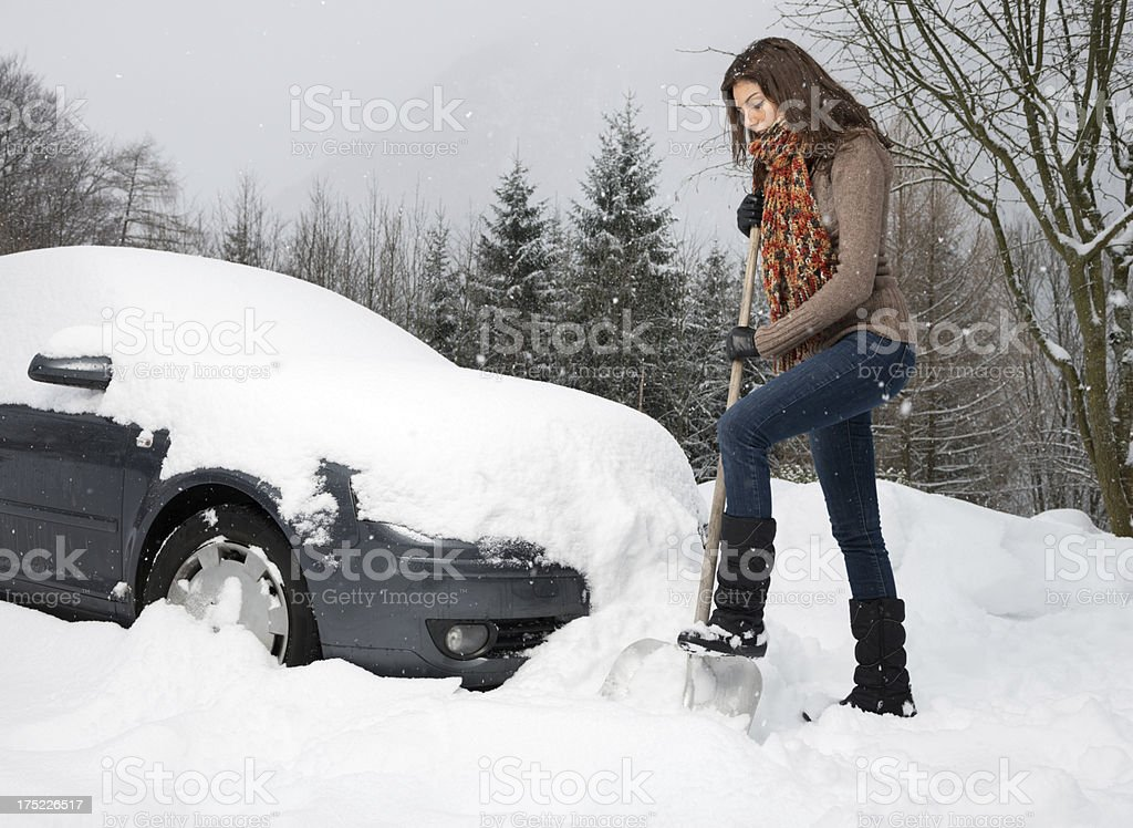 Woman freeing her car from Snow with a Shovel stock photo