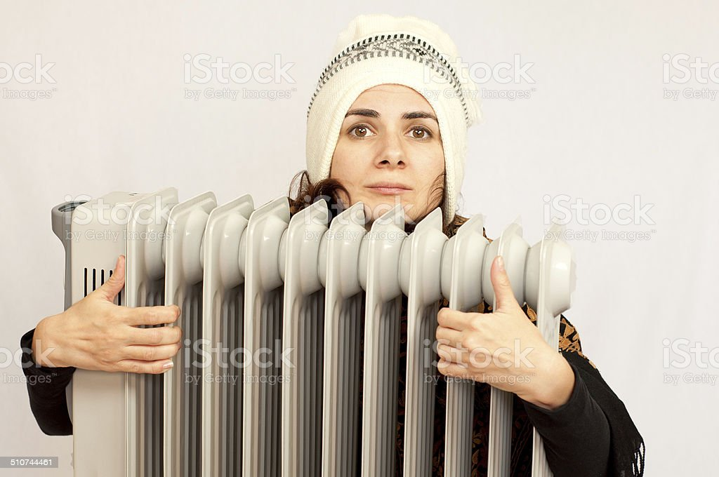 Woman freezing near the heater stock photo