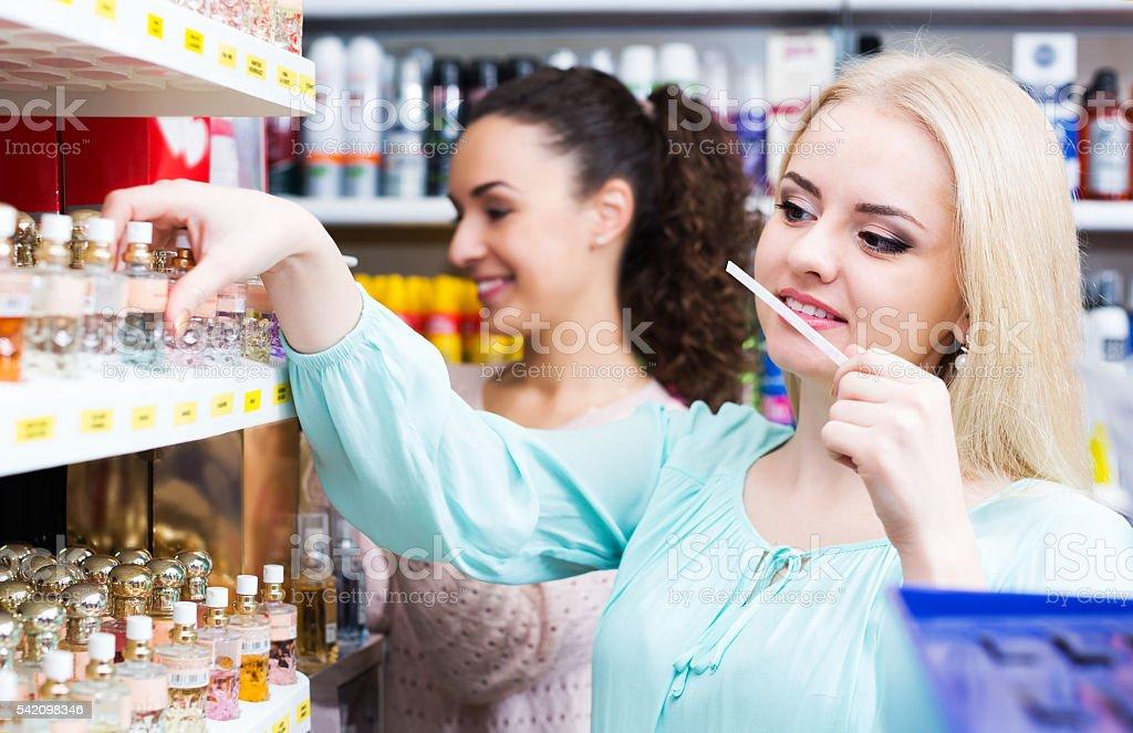 Woman friends buying perfume stock photo