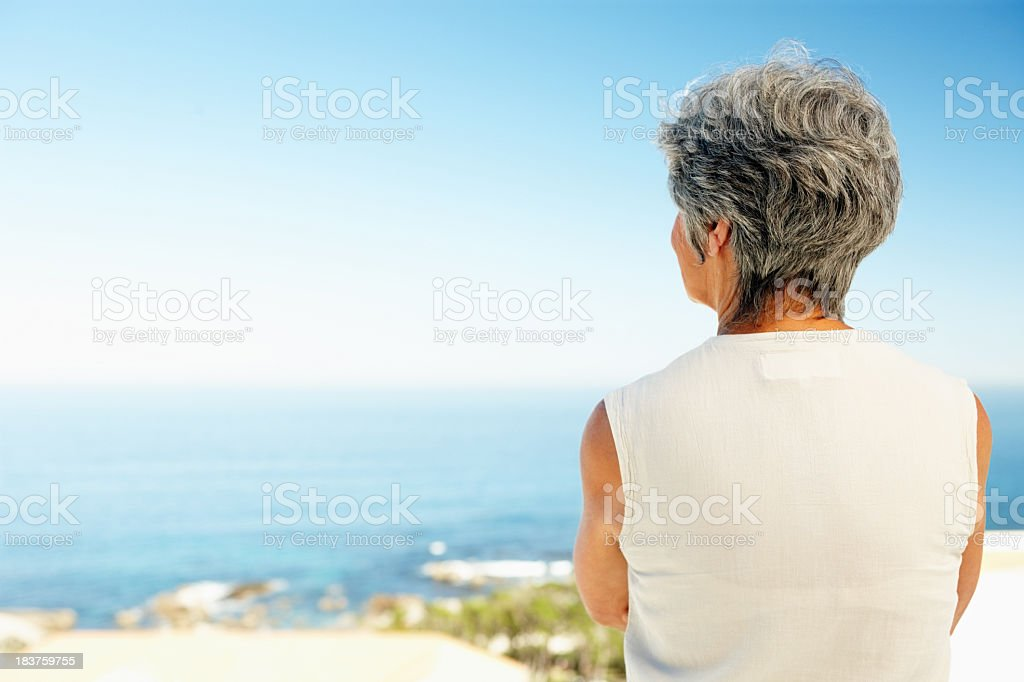 Woman from behind looking out over the ocean stock photo
