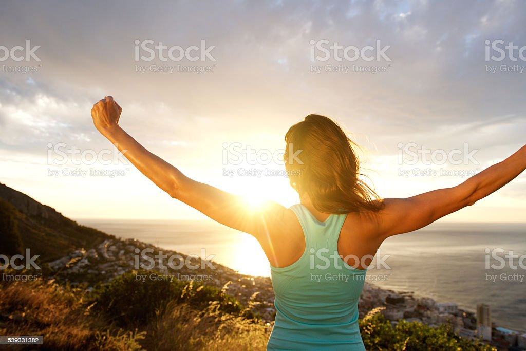 Woman from behind stretching out arms by sunrise stock photo