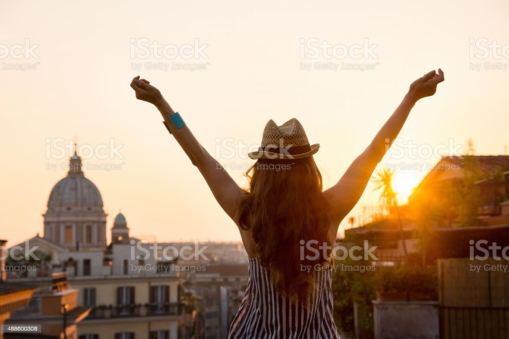 Woman from behind with outstretched arms in Rome at sunset stock photo