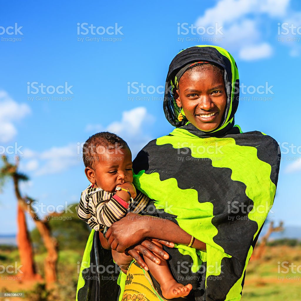 Woman from Borana tribe carrying her baby, Ethiopia, Africa stock photo