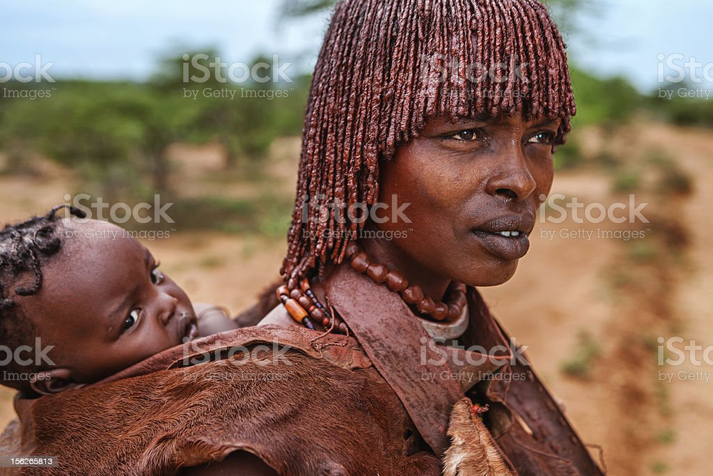 Woman from Hamer tribe holding her baby, Ethiopia, Africa stock photo