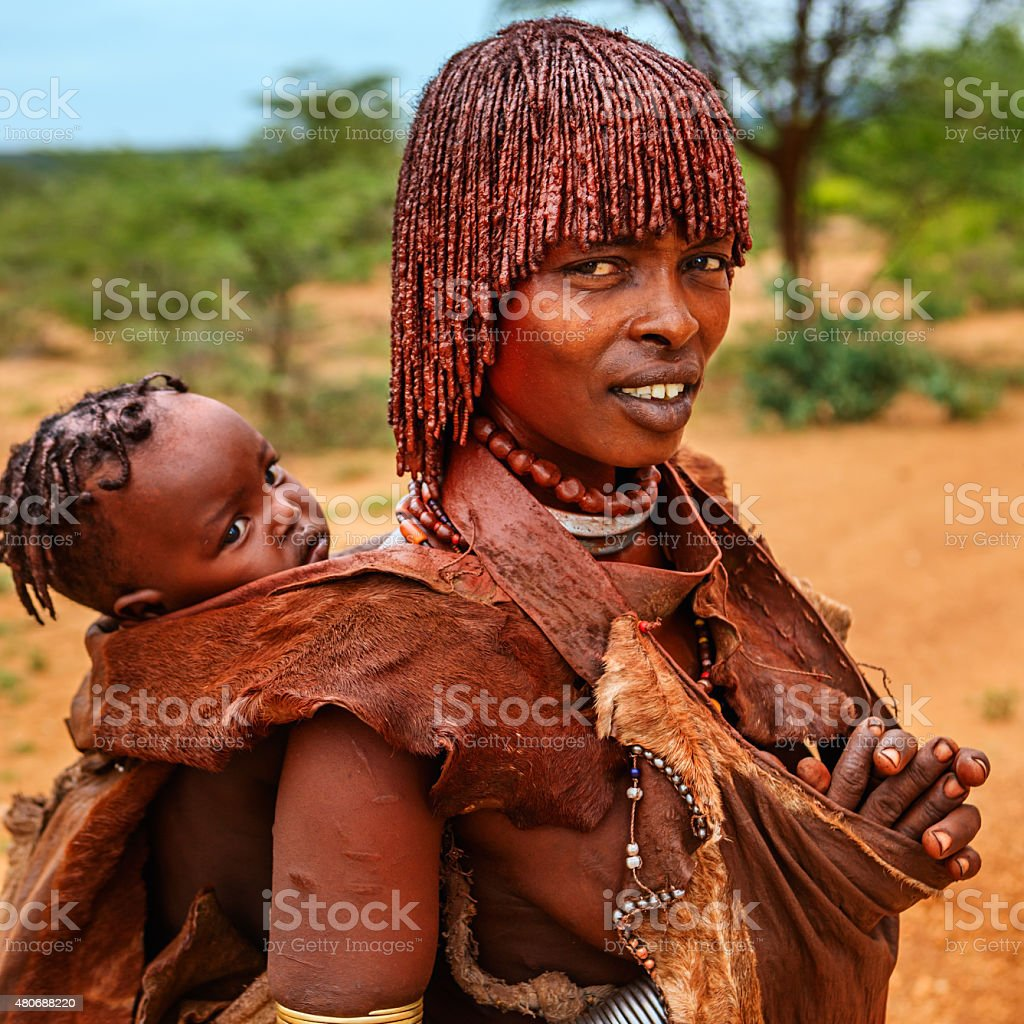 Woman from Hamer tribe carrying her baby, Ethiopia, Africa stock photo