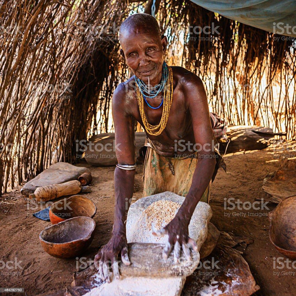 Woman from Karo tribe making sorghum flour, Ethiopia, Africa stock photo