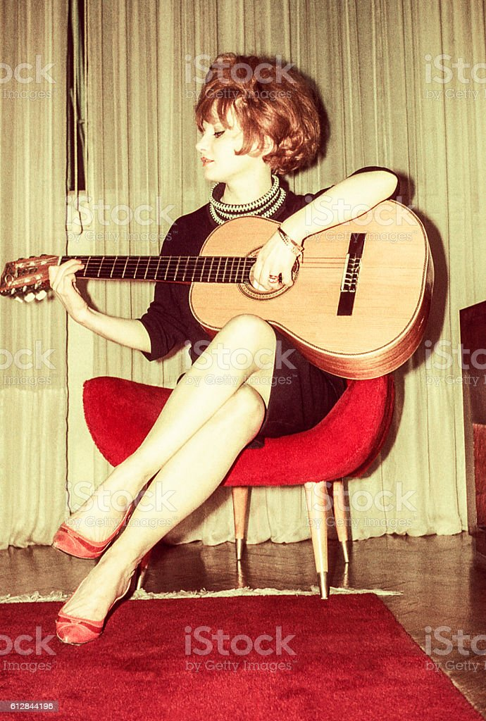Woman from the sixties playing guitar stock photo