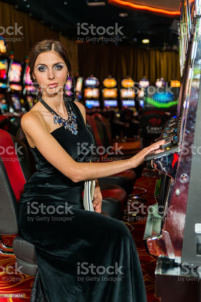Woman gambling in the casino on slot machines stock photo