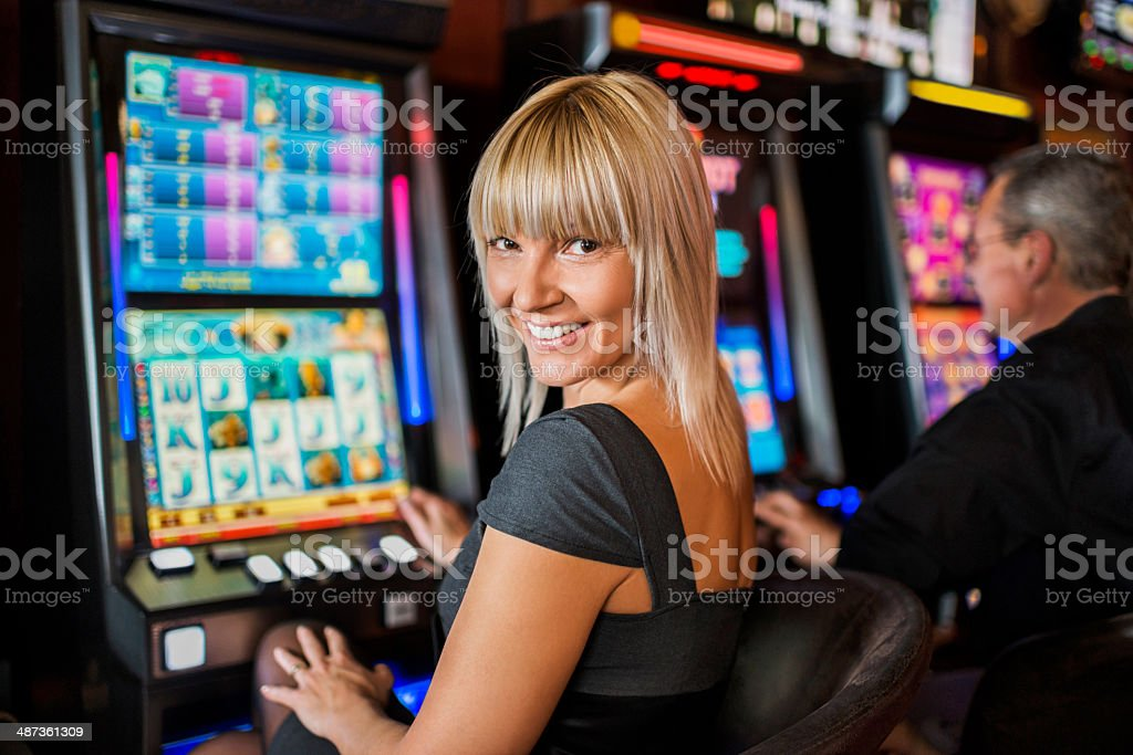 Woman gambling on slot machines. stock photo