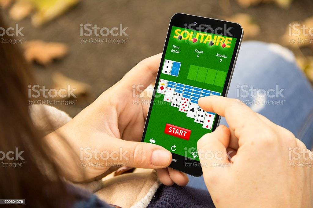 woman gaming cards on phone in the park stock photo
