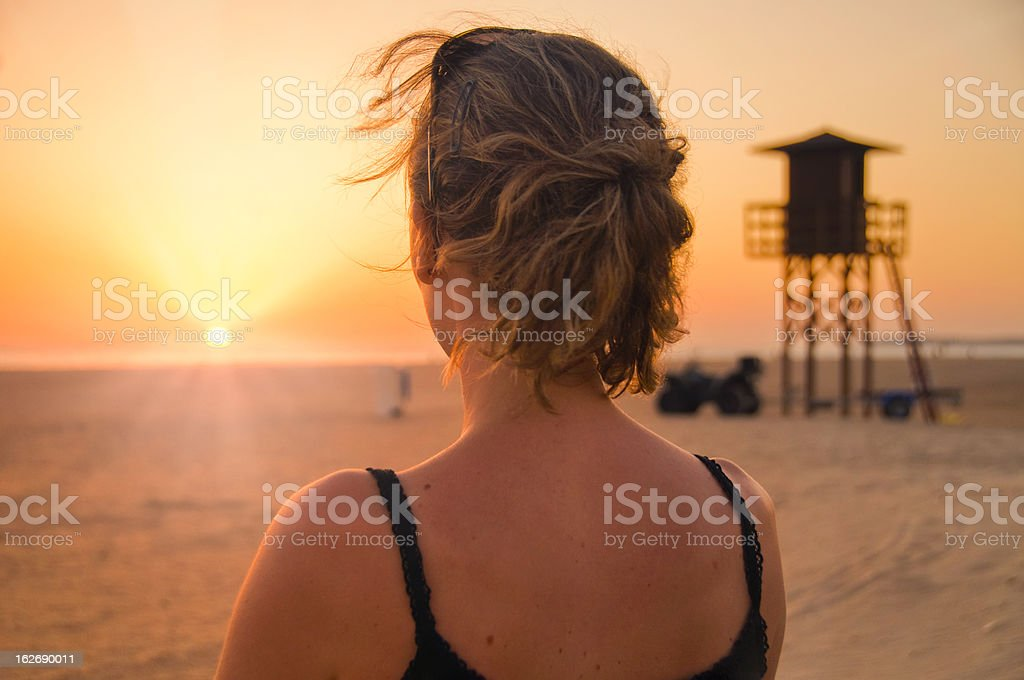 Woman gazing at the sunset stock photo
