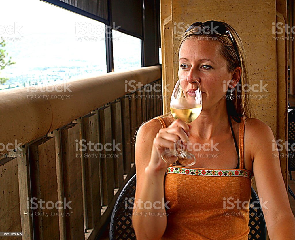 Woman gazing over balcony drinking white wine stock photo