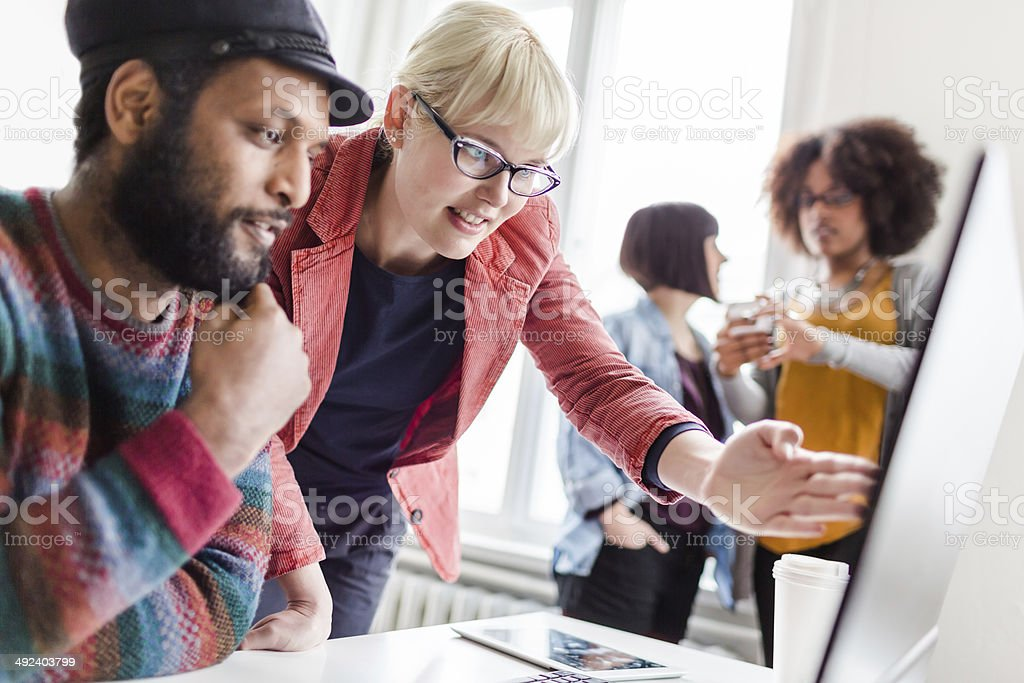 Woman gesturing to male coworker with two women in the back stock photo