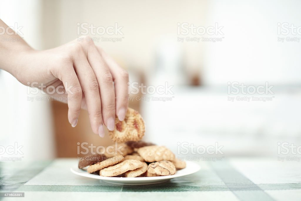 Woman get some cookie from the table royalty-free stock photo