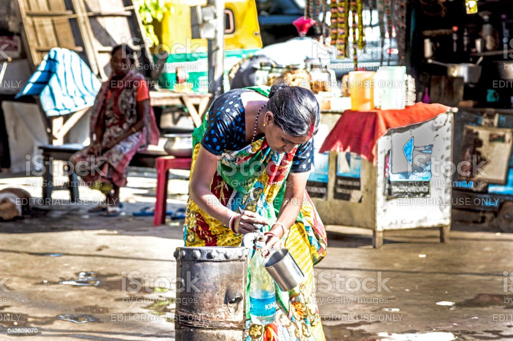 woman gets clean water from a hydrant in   Calcutta stock photo