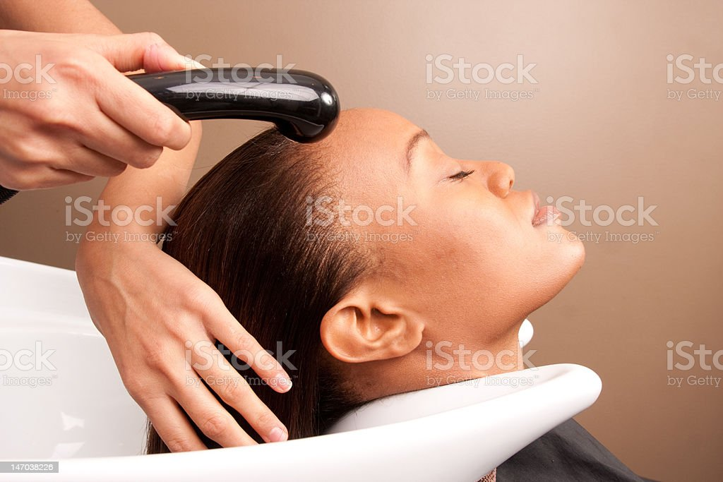 woman gets her hair washed at a salon stock photo