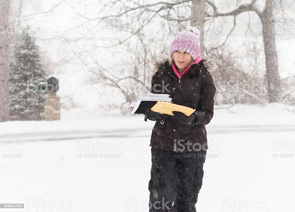 Woman gets mail during snowstorm stock photo