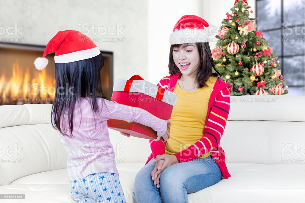 Cheerful Asian woman wearing a christmas hat and get a christmas...