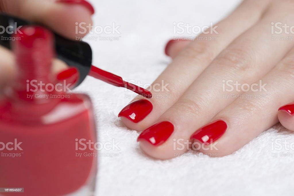 A woman getting a manicure with red nail polish stock photo