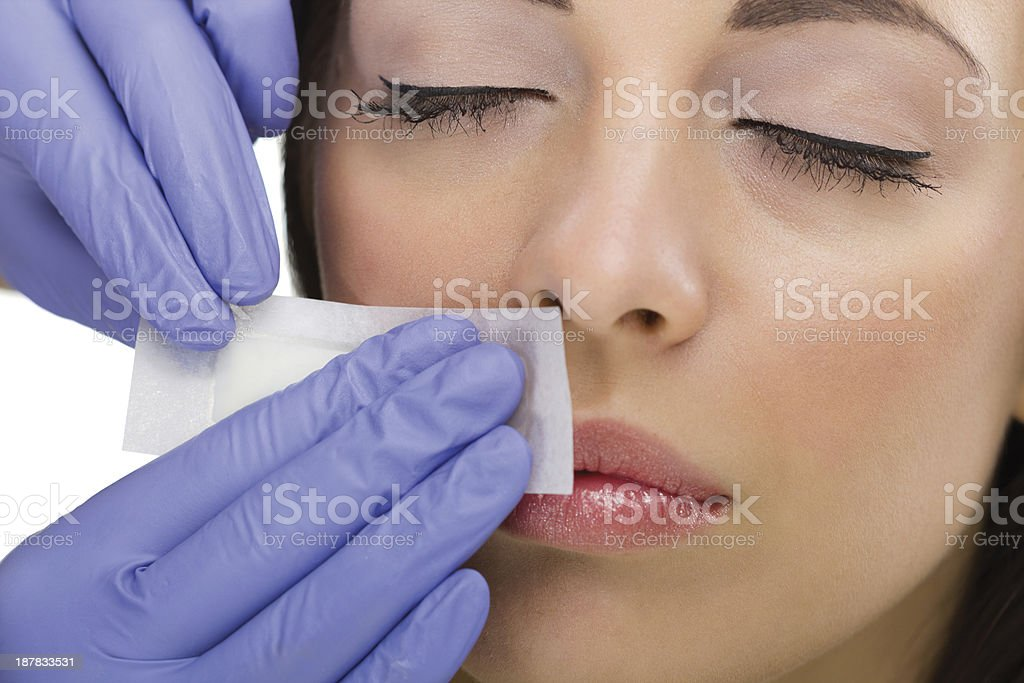 Woman getting a mustache wax by person with gloves stock photo