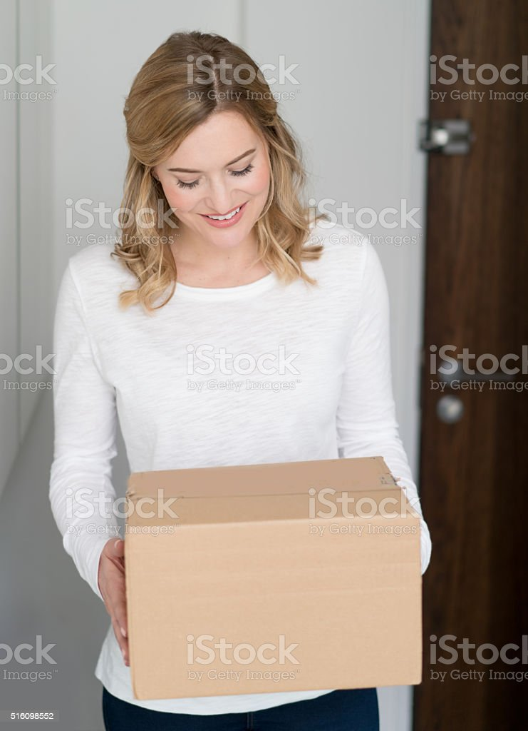 Woman getting a package at home stock photo