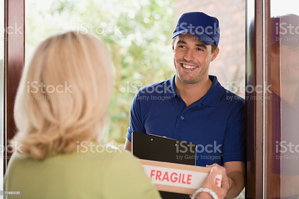 Woman getting a parcel from delivery man stock photo