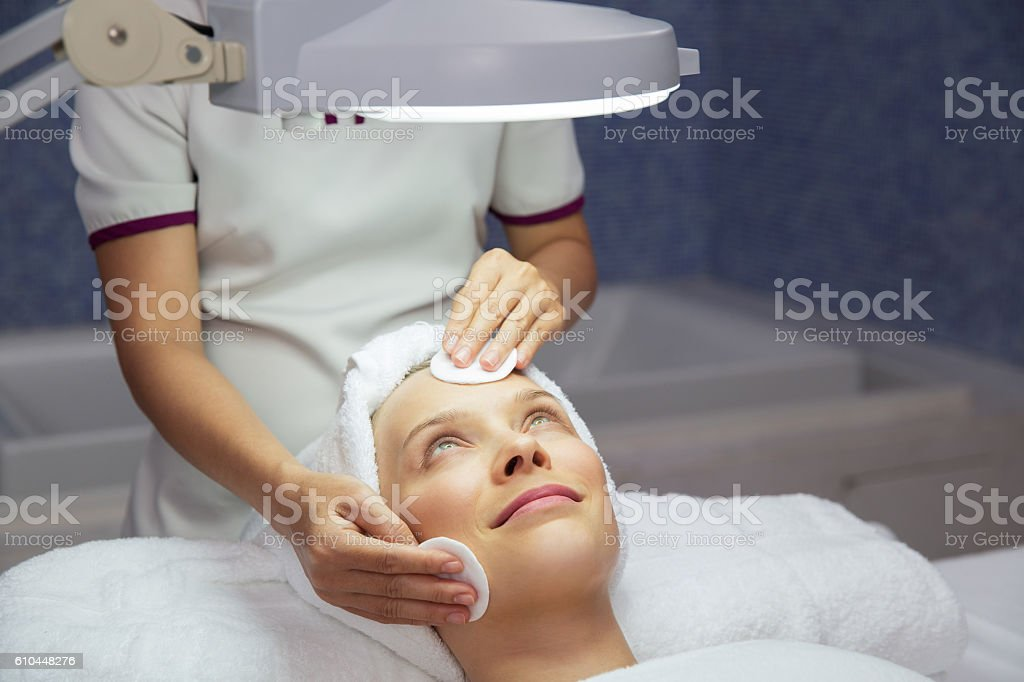 Woman Getting Facial Treatment in Beauty Salon stock photo