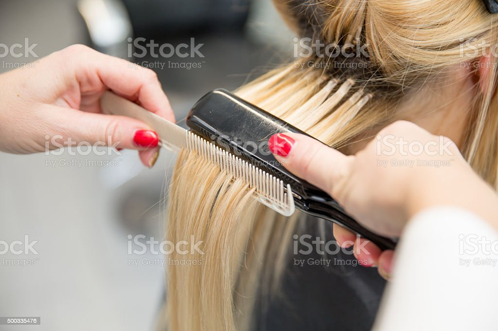 Woman Getting Hair Straightened at Hair Salon, Close-up stock photo