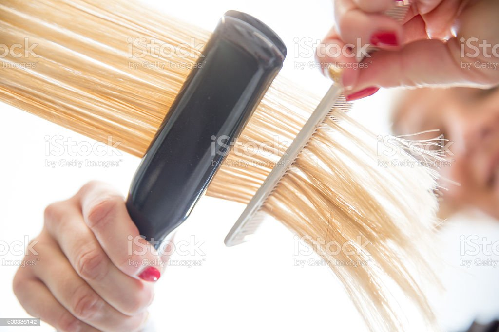 Woman Getting Hair Straightened at Hair Salon, Low Angle View stock photo