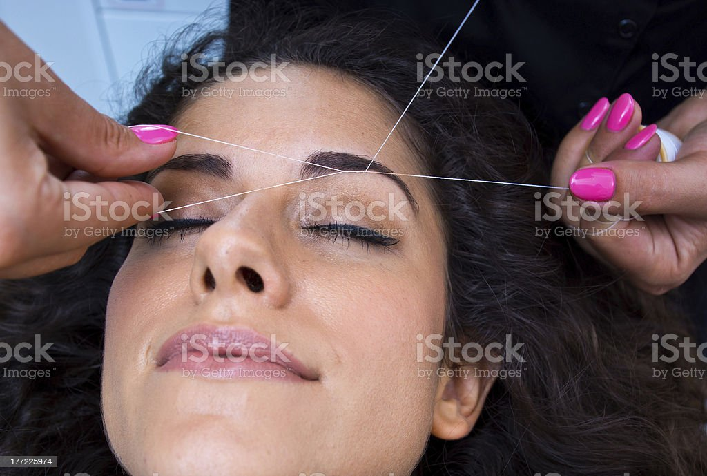 A woman getting her eyebrows threaded stock photo
