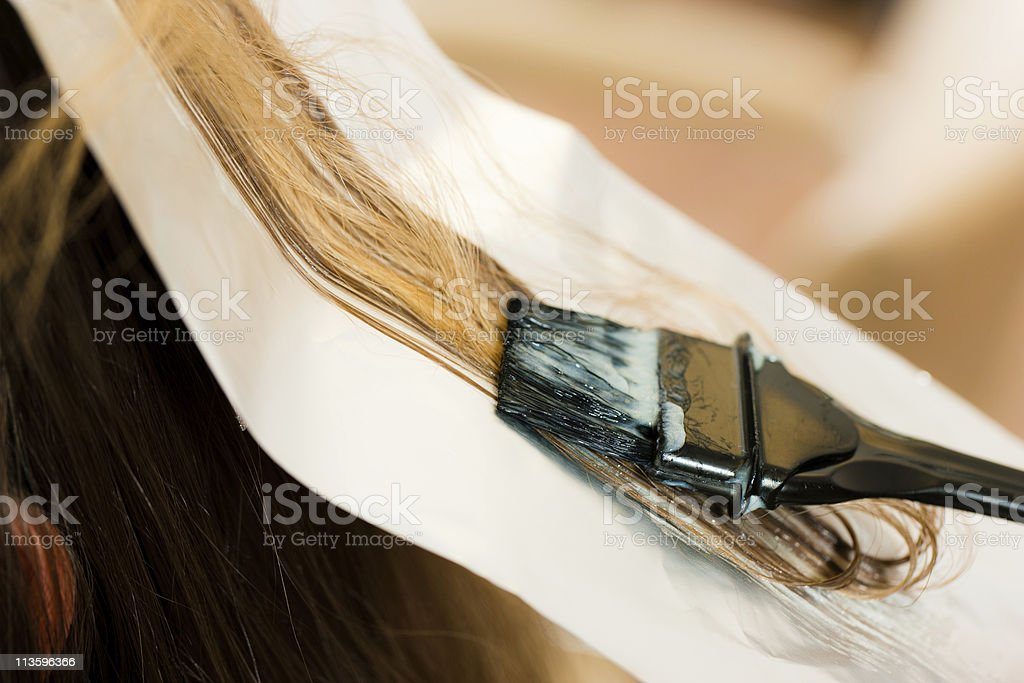 Woman getting her hair dyed color royalty-free stock photo