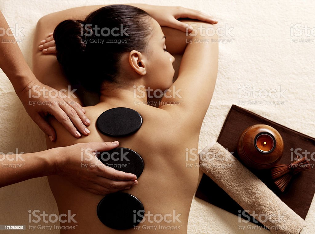 Woman getting hot stone massage in spa salon. stock photo