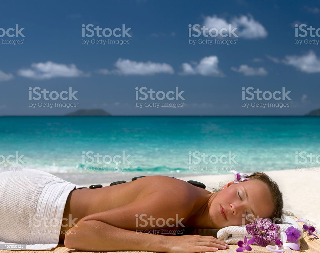 woman getting hot stone massage on the Caribbean beach royalty-free stock photo