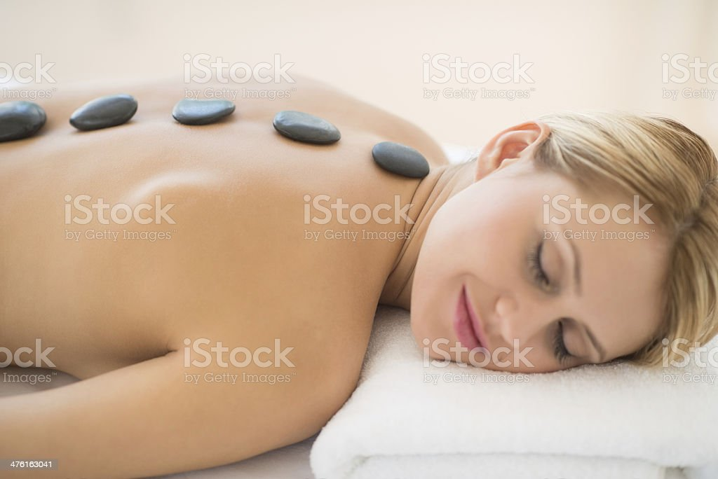 Woman Getting Hot Stone Therapy At Health Spa royalty-free stock photo