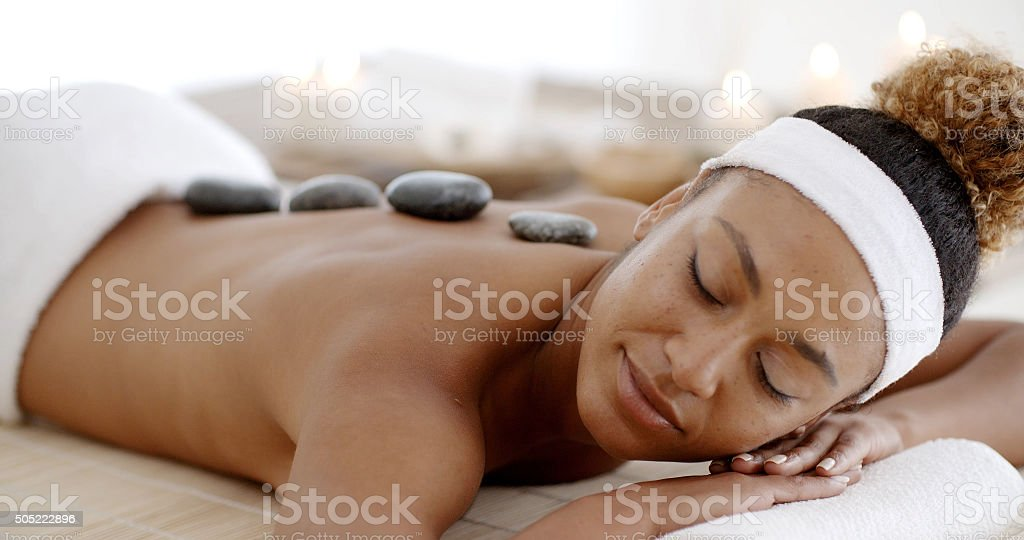 Woman Getting Hot Stones Massage At Spa stock photo