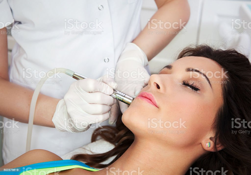 Woman getting laser face treatment in medical spa cente stock photo